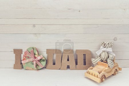 Fathers day background with Teddy Bear by car and cardboard lett