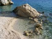 Croatian beach with giant rocks and small pebbles