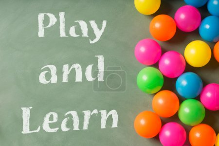 Green chalkboard and colorful balls. Play and learn
