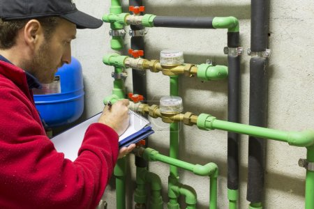 plumber at work making the consumption metering