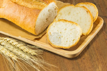Bread and wheat on the wood background, warm tonin...