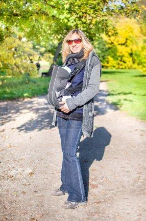 Photo pour Sac à dos porte-bébé au parc - image libre de droit