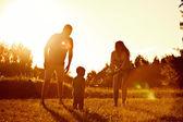 Šťastná rodina, otec, matka, syn a v přírodě, při západu slunce