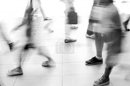 Photo for Motion blur people walking on white tiled floor. They are hurry in rush hour. Black and white filter - Royalty Free Image