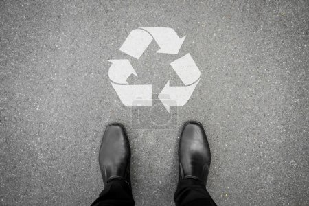 Black shoes standing in front of recycle symbol