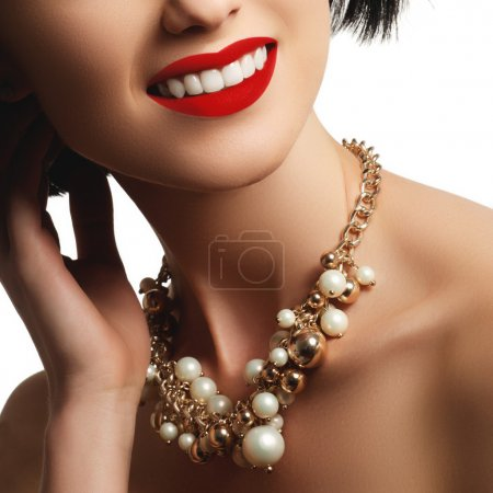 The beautiful woman in expensive pendant close-up. Beautiful young woman model with perfect makeup wearing jewelry. Fashion portrait of beautiful luxury woman with jewelry