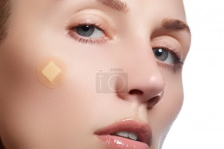 Close-up portrait of beautiful woman's purity face with natural make-up. Cute model with clean shiny skin. Beautiful young woman with clear-up patches or plaster on her skin. Skin care concept