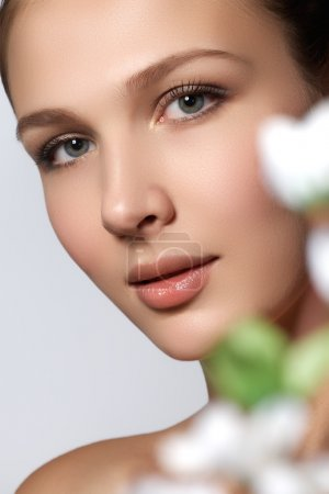 Beautiful Girl With Flowers.Beauty Model Woman Face. Perfect Skin. Professional Make-up.Makeup. Natural beauty face. Spa & wellness
