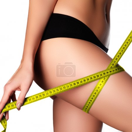 Woman measuring perfect shape of beautiful hips.Healthy lifestyles concept. Woman body part is being measured. Spa beauty part of body.Healthy lifestyle, diet and fitness. Perfect waist, butt and legs