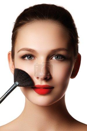 Photo pour Modèle beauté avec pinceau de maquillage. Maquillage lumineux pour femme brune aux yeux bleus. Beau visage. Une peau parfaite. Appliquer le maquillage - image libre de droit