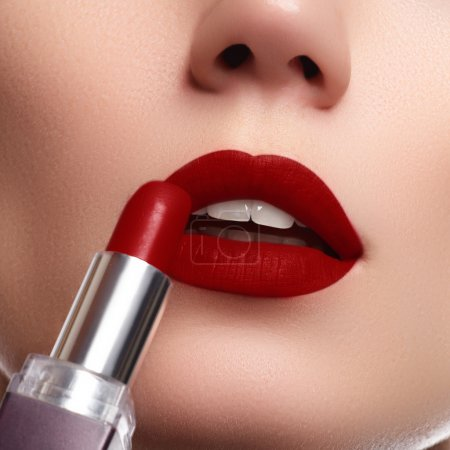 Photo for Extreme close up on model applying dark red lipstick. Makeup. Professional fashion retro make-up. dark red lipstick. Wine Lips - Royalty Free Image