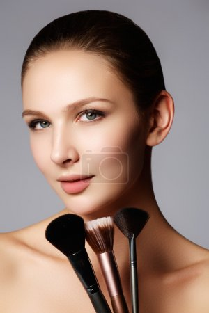 Photo pour Portrait Gros plan d'une femme d'appliquer la fondation tonale cosmétique sèche sur le visage en utilisant une brosse de maquillage. Belle femme avec pinceaux de maquillage près de son visage - isolé sur blanc - image libre de droit