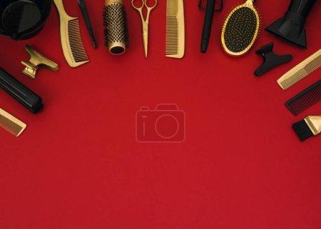 Photo pour Fond avec des outils de coiffure sur rouge. Accessoires de salon de coiffure noir et or, sèche-cheveux, peignes, ciseaux, fers à repasser. Bannière et modèle pour la conception avec espace pour le texte. - image libre de droit