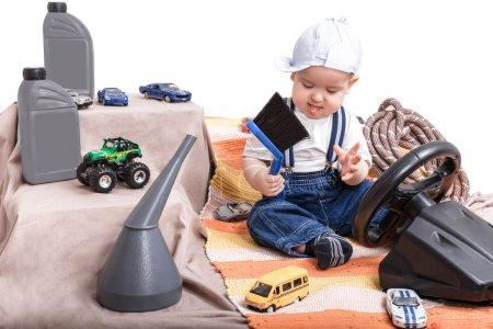 Foto de El niño en casa jugando en el auto. Viajes. Reparación de coches . - Imagen libre de derechos