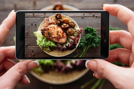 Photo for Food photography of baked pork with fresh vegetables. Home made food photo for social networks. Top view mobile phone photo of baked meat. - Royalty Free Image