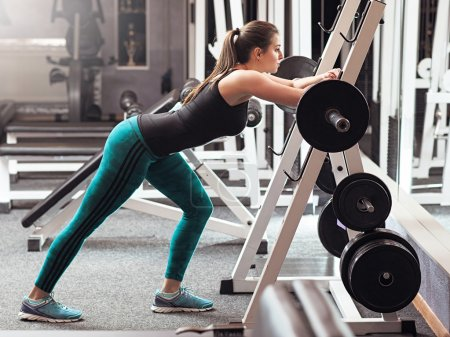 Weightlifter prepares to lift barbell in gym