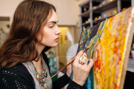 Photo for Creative painter paints a colorful picture. Closeup of painting process in art workplace. Painter paints in her studio. - Royalty Free Image