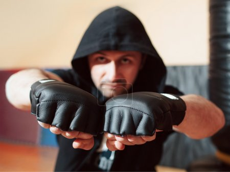 Photo for Aggressive mid adult street fighter in black hood ready to fight. Street fighter in training gloves shows his big fists. Man healthy sport lifestyle concept. - Royalty Free Image