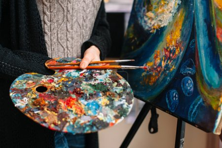 Closeup of artists paintbrush and mixing palette
