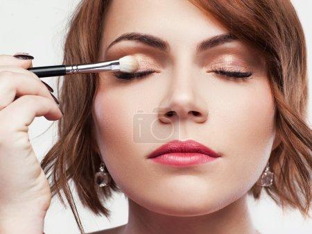 Photo pour Belle femme s'applique le fard à paupières couleur naturel doré avec brosse de maquillage. Oeil nu maquillage agrandi. Tête de jeune fille s'applique le fard à paupières brun brillant - image libre de droit