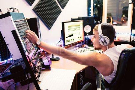 Photo pour DJ ajuste le matériel dans son studio d'enregistrement. DJ ajuste des équipements de musique avant de commencer la musique club record. Compositeur vérifie son panneau. Concept de service d'équipement de sonorisation numérique - image libre de droit