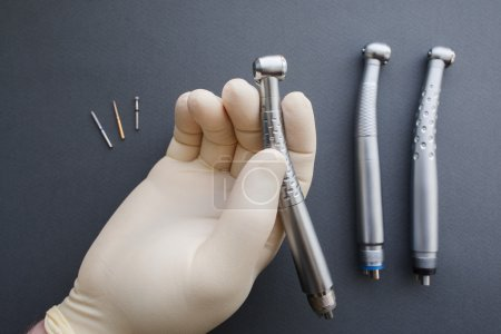 Dentist hand holding dental handpiece close-up