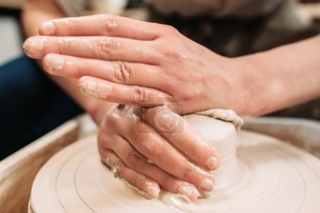 Working hands on potters wheel close-up