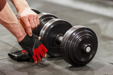 Man put on sport gloves before flexing dumbbells