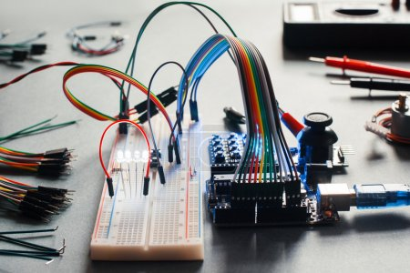 Photo for Electronic component connected with breadboard in laboratory. Electrical engineering with led and microcontroller on programmer workplace. Hacker conduct experiment with computer technologies - Royalty Free Image