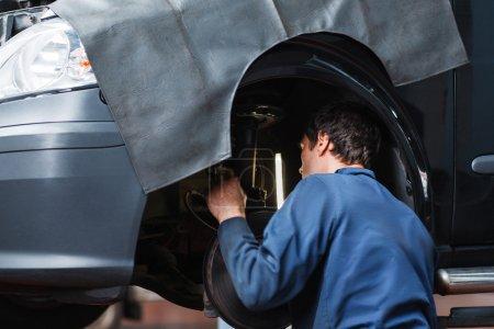 Mechanic inspecting car suspension system