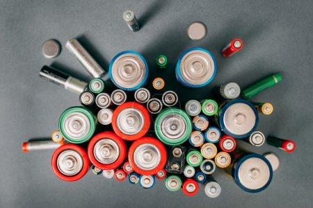 Photo pour Batteries colorées sur fond gris, vue de dessus. Énergie fond lumineux, gros plan - image libre de droit