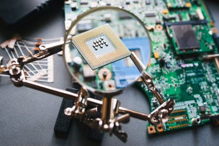 Photo for Desktop with broken disassembled laptop. Electronic parts of pc: motherboard, microprocessor. Analysis computer cpu through magnifying glass. - Royalty Free Image