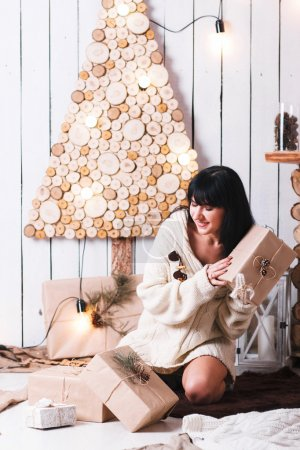Photo for Joyful girl in a white knit sweater unpacking Christmas gifts. Bright Christmas background is made of eco-friendly materials in a modern loft-style - Royalty Free Image