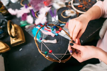 woman makes Dreamcatcher of sewing accessories.