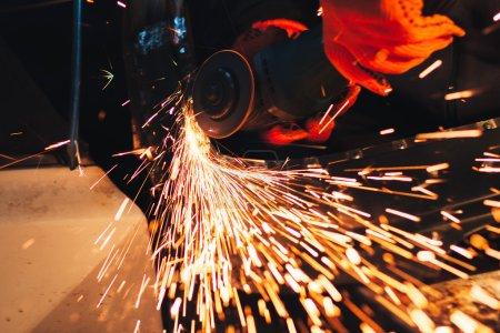 Photo pour Un ouvrier du bâtiment à l'aide d'une meuleuse d'angle produisant beaucoup d'étincelles. Travail professionnel metall - image libre de droit