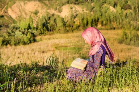 Muslim Woman Reading Holy Quran and praying outdoors