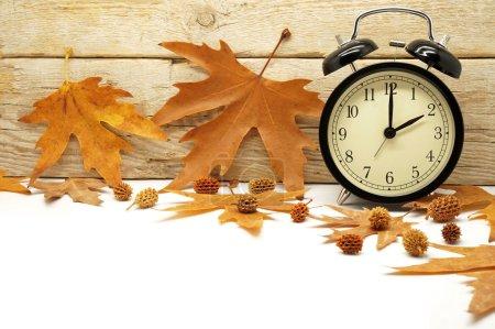 Photo pour Feuilles d'érable et réveil sur fond en bois - image libre de droit