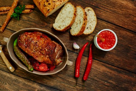 Photo pour Cook connu steakhouse, filet de porc cuit au four avec ail et épices, servi avec légumes frits, pain grillé aux graines est coupé et se trouve proche - image libre de droit