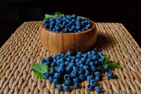 Photo pour Sur une petite table est des ustensiles en bois osier lumineuse, décorée avec des baies, des feuilles de menthe, à proximité de la plaque est épars de bleuets - image libre de droit