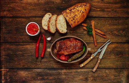 Photo pour Vue de dessus d'une femme au foyer dans le four cuit de boeuf aux légumes, les viandes cuites dans une sauce tomate d'ail et les épices, cuits au four à pain avec des graines de tournesol - image libre de droit