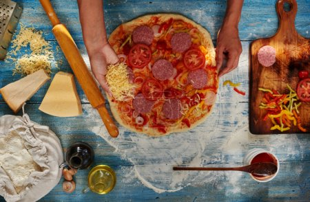 Photo for Womens Hands chef Italian restaurant pizzas, lays stuffing, sprinkle with cheese, near pitsey is board on which is chopped peppers and tomatoes - Royalty Free Image