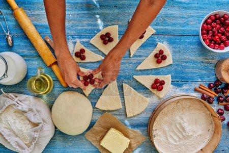 Photo pour Fille assistent cuire doucement déposer les cerises feuilletées, dénoyautées, après que la pâte est enveloppée - image libre de droit
