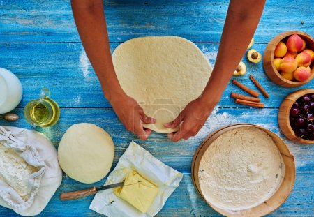 Photo for Young girl chef kneads the dough  and rolled with a rolling pin and rolled - Royalty Free Image