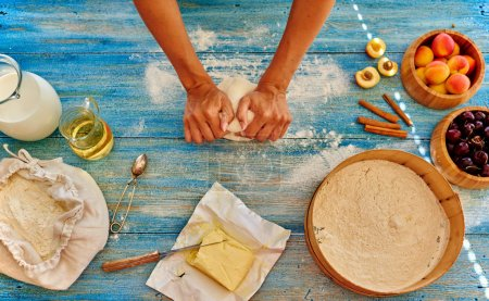 Young girl chef kneads  and rolling the dough with pin