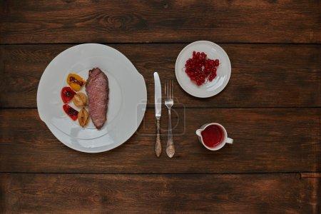 Photo pour Cook steakhouse branché Agneau cuit sur le grill, servie sur une plaque blanche svehru versé filet avec sauce aigre-douce berry - image libre de droit