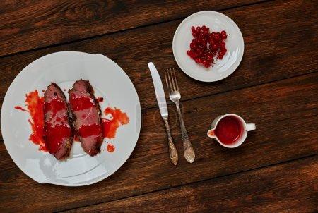 Photo pour Sur une table en chêne foncée texturale, qui dessert dîner sur une plaque blanche sur deux morceaux de boeuf frit à tir rapide, debout à côté de la sauce - image libre de droit