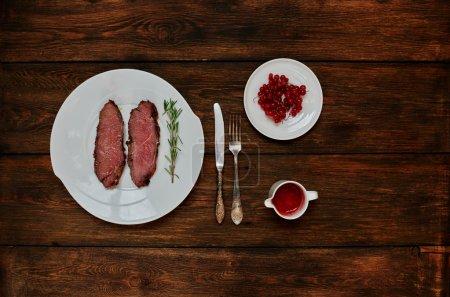 Photo pour Sur une table en bois foncée est une plaque avec deux steaks rares, debout à côté de la sauce tomate avec l'ajout de piments forts - image libre de droit