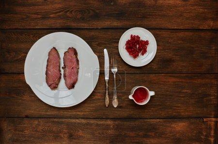 Photo pour Sur une table en bois foncée est une plaque avec deux steaks Medium rare, debout à côté de la sauce tomate avec l'ajout de piments forts - image libre de droit