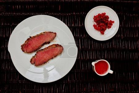 Photo pour Sur la table est une plaque avec deux steaks légèrement grillés, sont servis aux côtés de coutellerie à côté de la sauce aux baies rouges fraîches - image libre de droit