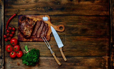 Photo for Appetizing piece of pork, chopped into small pieces, lying on a wooden table textural near cherry tomatoes as a garnish for baked meat - Royalty Free Image